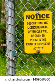 Yellow and black neighborhood crime warning sign posted on chain link fence with wooded background.