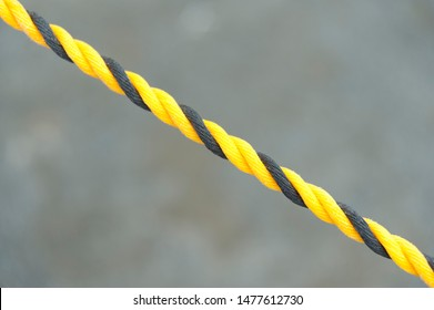 Yellow and Black Nylon Rope in Close-up. Nylon rope in diagonal direction. Isolated on blurred background. Copy space.