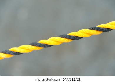 Yellow and black nylon rope. Nylon rope in diagonal direction. Isolated on blurred background. Close-up. Copy space.