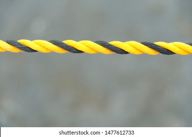 Yellow and black nylon rope. Nylon rope in horizontal direction. Isolated on blurred background. Close-up. Copy space.