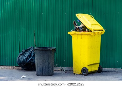 Yellow and black plastic Trash can with green metal sheet fence on concrete road