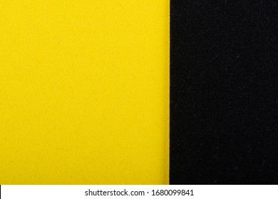 Yellow and black sheet of colored velvet paper. Bright color background. Horizontal orientation. Square and vertical strip. Top view flat lay with copy space.