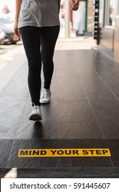 """Yellow and black warning sign  """"Mind Your Step"""""""