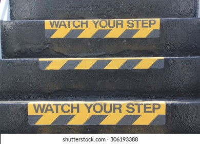 """Yellow and black warning sign on stairs stating """"Watch your Step"""" signifying a potential trip hazard, steep stairs and care to be taken when going up or down stairs"""