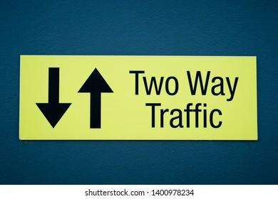 Yellow and black warning sign with text TWO WAY TRAFFIC and two arrows on blue wall