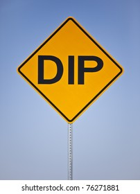 A yellow and black warning or traffic or street sign that says DIP on a silver metal post by the side of the road