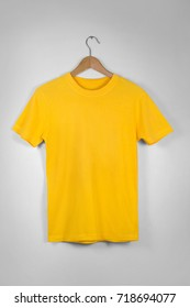 Yellow Blank Cotton Tshirt Hanging Center Gray Concrete Empty Wall Background with clipping path
