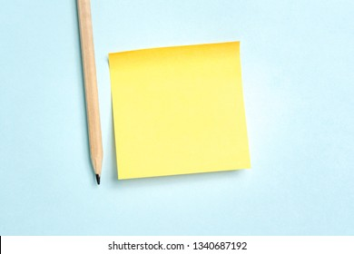 Yellow blank empty sheet of paper message with a pencil on blue background for text. Negative space. Top view copy space.