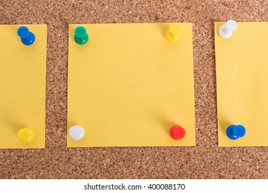 Yellow blank note papers with pin on wooden board background