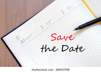 Yellow blank notepad on office wooden table Save the date concept