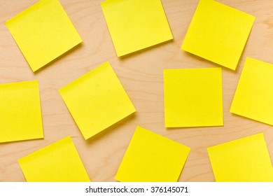 Yellow blank postit notes randomly glued on wooden board