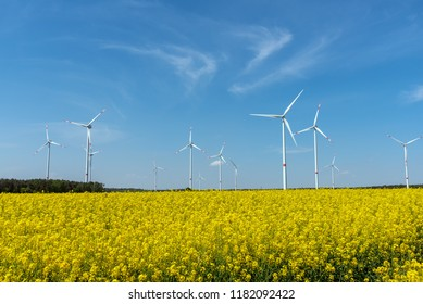 Yellow blooming oilseed rape and some wind energy plants seen in rural Germany