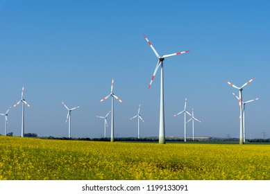 Yellow blossoming rapeseed and some wind energy plants seen in rural Germany