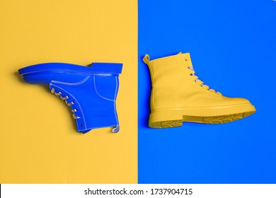 Yellow and blue boots. Top view flat lay. Creative footwear design concept.