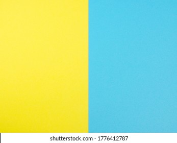 yellow and blue colored paper for texture background, two pastel colored paper are placed symmetrical parallel, flat lay close up top view