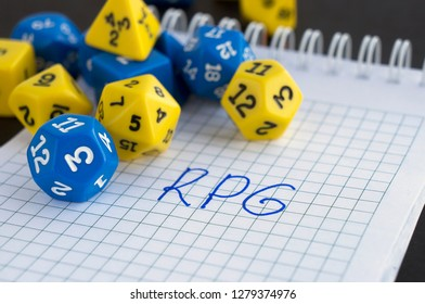 Yellow and blue dices for rpg, board, dnd, or tabletop games; a notepad with letters RPG written on it.