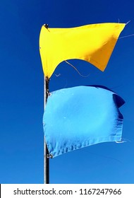 Yellow and Blue flags flying at the beach warning beach goers of dangerous surf and aquatic hazards.