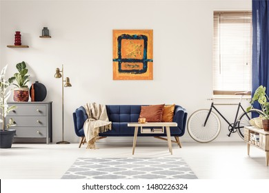 Yellow and blue painting hanging on white wall in bright living room interior with grey cupboard, gold lamp, sofa with blanket and pillows, and bike standing under window with blinds