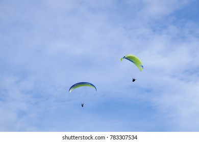 Yellow blue paraglider flying against the blue sky with white clouds at skogafoss iceland during  summer