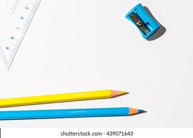 Yellow And Blue Pencils And A Ruller Over White Paper