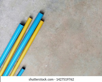 Yellow and blue PVC pipe lay on concrete floor. Construction material. Polyvinyl chloride tube yellow color use for electric wire and blue color use for water system.  Rigid PVC pipe.