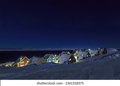 Yellow, blue, red and green inuit houses covered in snow at the fjord under the starlight sky, Nuuk city, Greenland