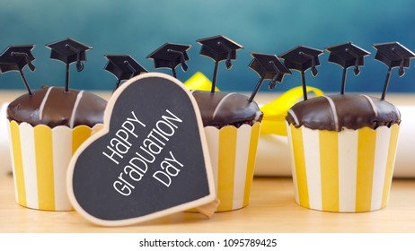 Yellow and blue theme graduation party cupcakes with cap hats toppers and decorations.