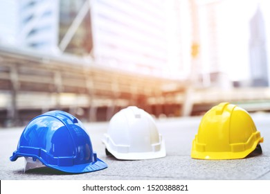 yellow, blue and white hard safety wear helmet hat in the project at construction site building on concrete floor on city. helmet for workman as engineer or worker. concept safety first