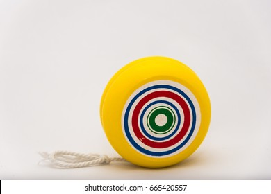 yellow, blue, white, red and green wooden yo-yo on a white background