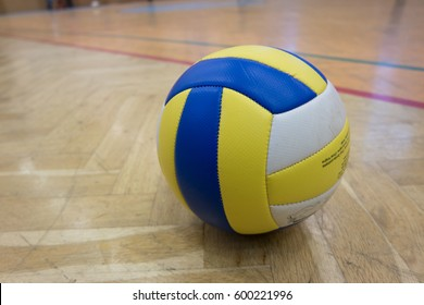 Yellow Blue White volleyball on the ground in the school gym