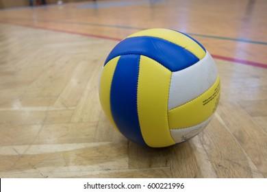 Žlutý modrý bílý volejbal na zemi ve školní tělocvičně