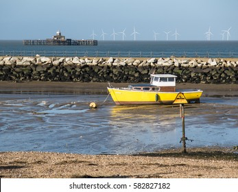Yellow boat moored in Herne Bay, Kent, England, there is a sing warning about mud and harbour arm, wall of stones. The remains of the old pier can be seen on the horizon and wind turbines.
