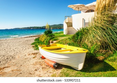 Yellow boat on beautiful Bombarde beach, Alghero bay, Sardinia, Italy
