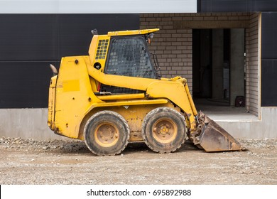 Yellow bobcat or skid loader on construction site
