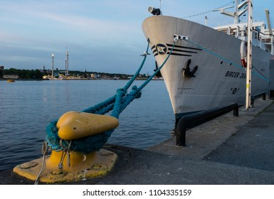 Yellow bollard docks/Ship cruiser docked with blue bowline to a yellow bollard on the quay of Sodermalm island in the Baltic archipelago. Stockholm, Sweden, May 22, 2018.