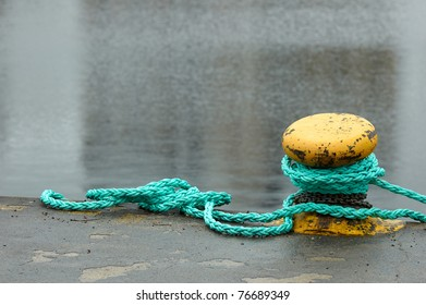 Yellow bollard with green rope attached