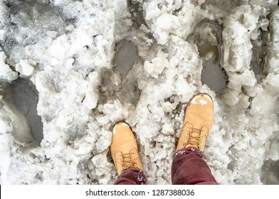 yellow boots and slush on a snowy road as an obstacle to the passage of pedestrians, printed footprints and water