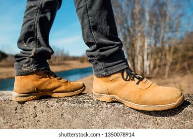 Yellow boots with thick soles for hard work and walking, man in shoes outdoors