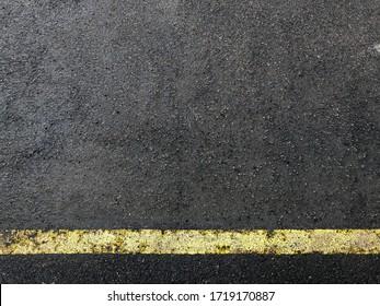 A yellow boundary line on the wet asphalt. Texture, wallpaper