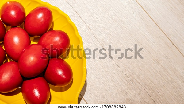 Yellow bowl with red Easter eggs isolated on a wooden table. Red painted eggs as symbol of the holiday of Easter. Top view. Copy space