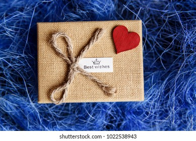 Yellow box with gift and the red heart on it on the blue background