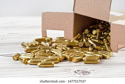 Yellow brass gun ammo spilled from paper carton box on white boar desk - close up
