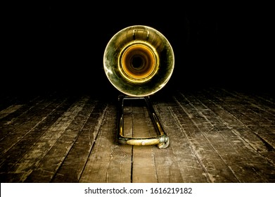 yellow brass instrument trombone lies on the wooden floor of the stage. front view on the bell