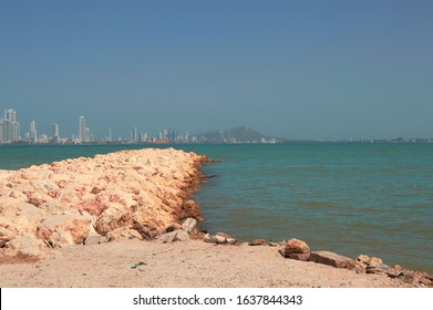 Yellow breakwater of coral rock with blue sea cafe beach near the city of Cartagena de Indias
