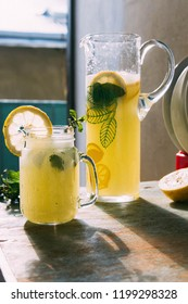 Yellow bright sunny lemonade with mint in a jar