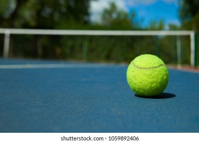 Yellow bright tennis ball is lying on on blue carpet of opened court during sunny day. Made for playing tennis. Contrast image with satureted colors. Concept of tennis outfit photografing.