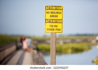 Yellow and Brown Boardwalk Sign Warning No Railing Ahead