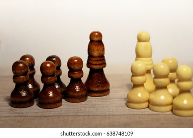 yellow and brown chess pieces. pawns the following bishop. segregated.
