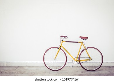 Yellow brown vintage style bicycle on white wall background. Old bike standing parked near a home with copy space. Nostalgic color effect
