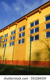 Yellow building behind a metal grid fence